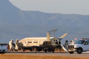 I tecnici al lavoro sull'X-37B appena atterrato sulla pista della base dell'USAF di Vandenberg, il 16 Giugno 2012, dopo aver concluso la sua seconda missione, durata 469 giorni.  Da notare le misure precauzionali per evitare di venire a contatto con i residui dell'Idrazina (C) Boeing