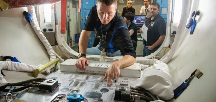 Terry Virts lavora al pannello UIA nel mockup dell'airlock per le tute EMU della ISS. Fonte: NASA/Stafford - Foto: jsc2012e238218
