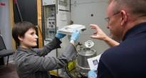 Samantha Cristoforetti sostituisce il contenitore dei rifiuti solidi della toilette nel mockup della ISS al JSC. Fonte: NASA/Harnett