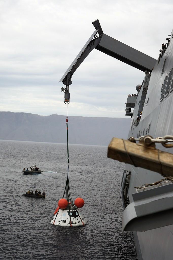 """Il boilerplate di Orion viene delicatamente sollevato dall'acqua con la gru per verificare l'efficacia della procedura di recupero tramite una """"cesta"""" nel corso di un'evoluzione dell'Underway Recovery Test 2 in prossimità della USS Anchorage nell'Oceano Pacifico al largo delle coste di San Diego, California il 3 Agosto 2014. Image Credit:  NASA/Kim Shiflett"""