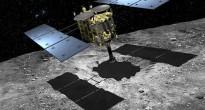 """Un'immagine artistica della sonda Hayabusa 2 mentre ricava un campione dal satellite """"1999 JU3"""". Credit JAXA/Akihiro Ikeshita"""