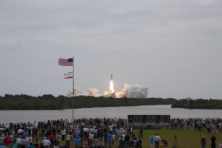 L'iconico orologio posto all'esterno della sala stampa del KSC è stato testimone di buona parte della storia dell'satronautica. In questa immagine il lancio dell'ultima missione del programma Space Shuttle, l'STS-135, decollata dal KSC l'8 Luglio 2011. (C) KSC/NASA