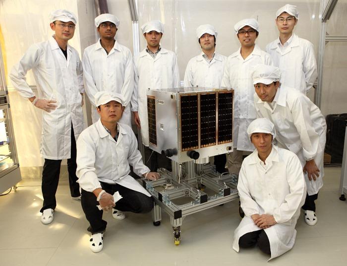 Il gruppo di ingegneri che ha realizzato Hodoyoshi-1 posa accanto al satellite (Image: University of Tokyo/AxelSpace)