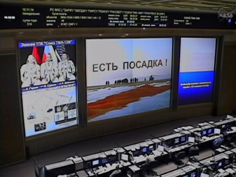"""Un'immagine della sala di controllo russa subito dopo l'atterraggio della Sojuz TMA-13M. La scritta in cirillico sullo schermo principale significa """"Atterraggio riuscito"""". Image Credit: NASATV"""