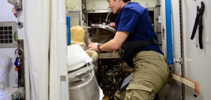 Samantha Cristoforetti rabbocca l'acqua di scarico della toilette del Nodo 3. Credit: ESA/NASA
