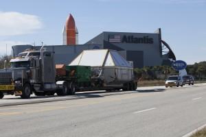 Il container con la capsula Orion passa di fronte allo Space Shuttle Atlantis Building del Kennedy Space Center Visitor Complex prima di fare il suo ingresso al KSC. Photo credit: NASA/Dimitri Gerondidakis