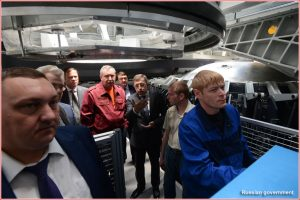 Head of GKNPTs Khrunichev Andrei Kalinovsky explains the work of machinists welding components of the Angara rocket at PO Polyot to Deputy Prime Minister Dmitry Rogozin (in red jacket) and head of Roskosmos Igor Komarov (to Rogozin's left).