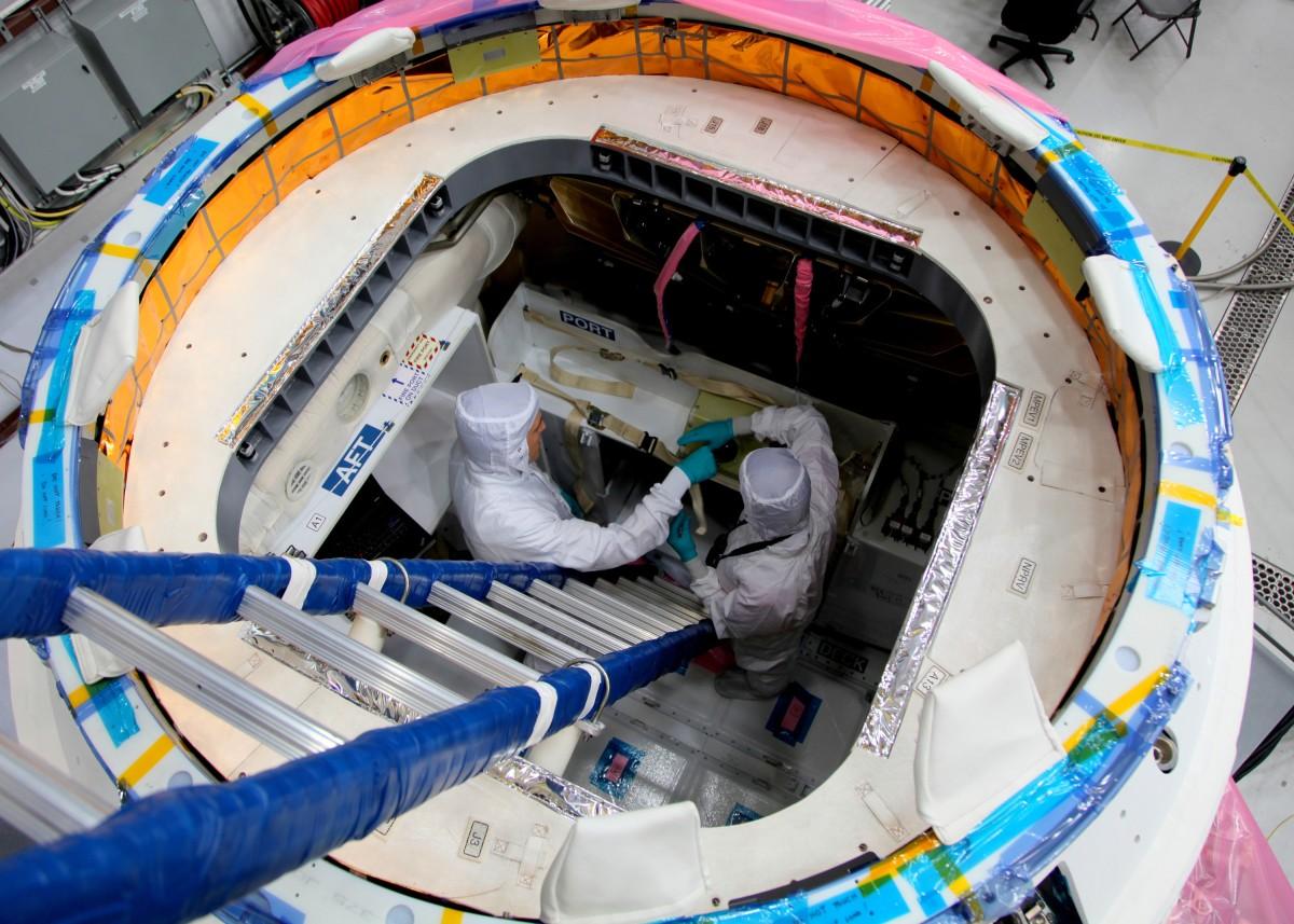Operazioni di carico del payload in una capsula Dragon. Credit NASA