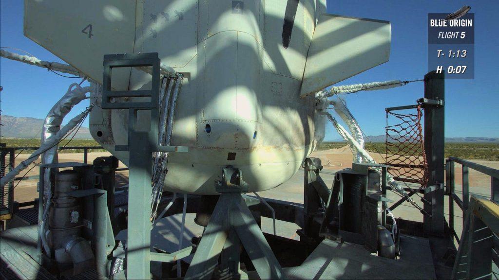 La base del New Shepard al momento del primo hold. La pinna a destra sta ruotando. Su quella a sinistra si nota il 4 che indica il numero di voli completati con successo (Credit: Blue Origin)