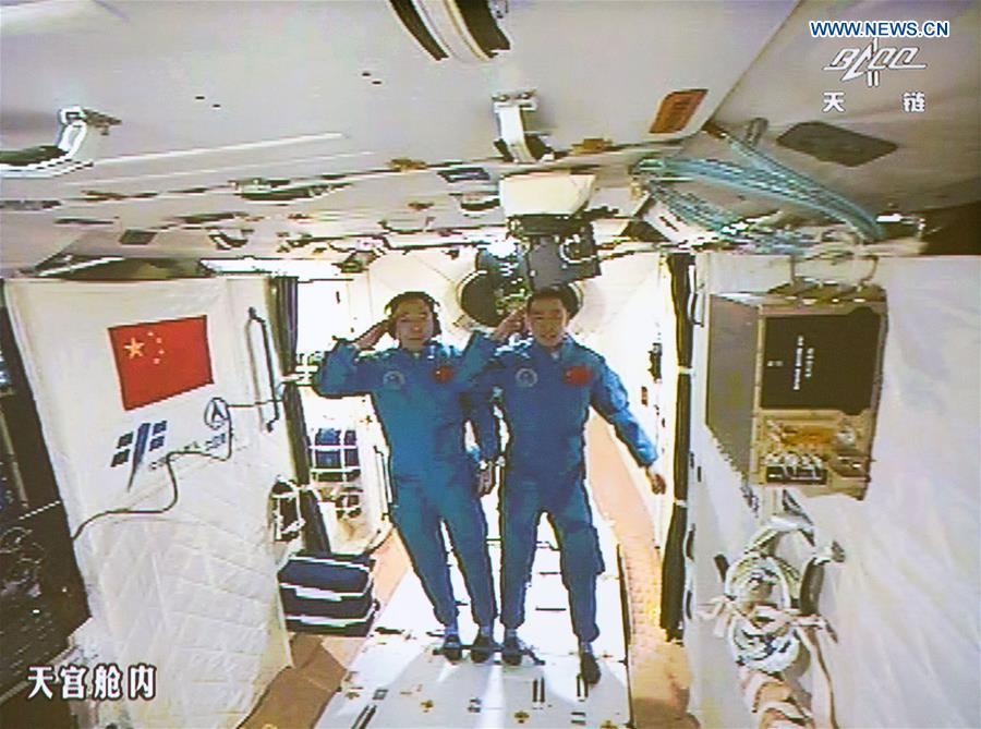 Jing Haipeng e Chen Dong fanno il saluto militare poco dopo il loro ingresso in Tiangong-2 (Credit: Xinhua/Ju Zhenhua)